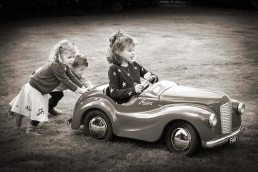 family-photography-leamington-children playing in pedel car