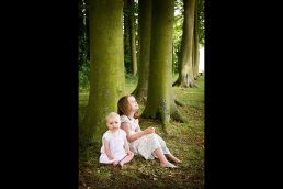 Children sitting under a tree, from a Cotswolds photoshootCotswolds